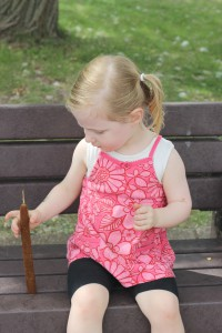 child playing with cattail on bench